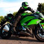 mężczyzna w stroju motocyklowym i kasku jadący na motocyklu typu ścigacz